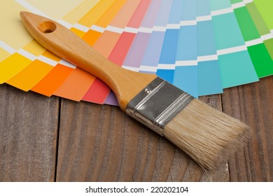 Color chart guide for renovation with brush on wooden surface