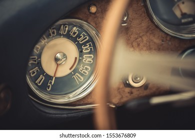 Color close up shot of a blue speedometer on a vintage car's dashboard.