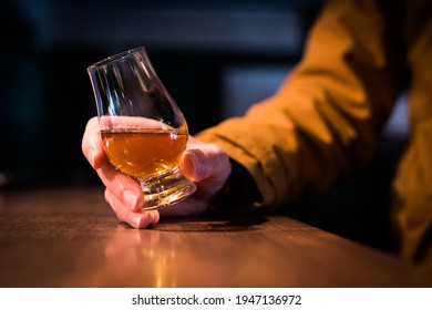 Color close up shot a hand holding a whisky glass on a wooden table, with shallow depth of field.