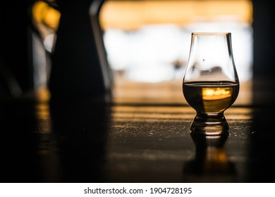 Color close up shot of a whisky glass on a wooden table, with shallow depth of field.