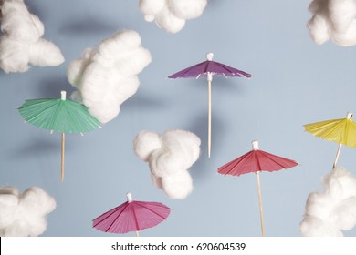 Color cocktail umbrella flying in the air between cotton wool as cloud