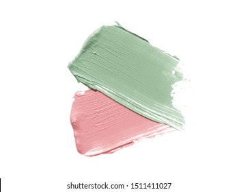Color corrector strokes isolated on white background. Green and pink colour correcting cream concealer smudge smear swatch sample. Makeup foundation creamy texture