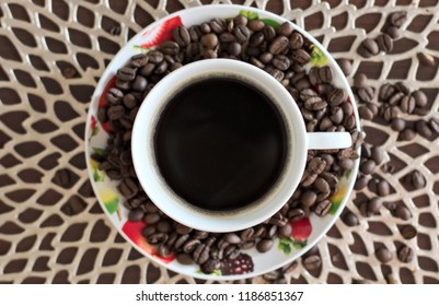 A color cup of coffee surrounded by coffie beans. Top view.