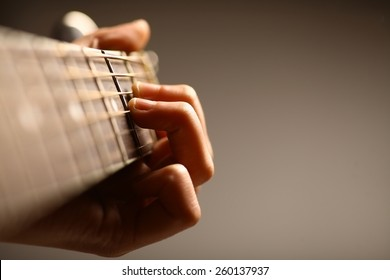 Color detail of hands playing of an old, acoustic guitar.