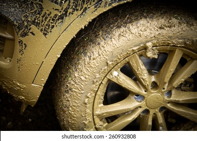 Color detail shot of an off-road car's wheel, covered in mud.