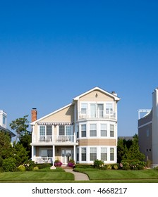 Color DSLR picture of isolated luxury vacation beach house on the New Jersey shore.  Green grass lawn and a clear blue sky background. Vertical orientation with copy space for text.