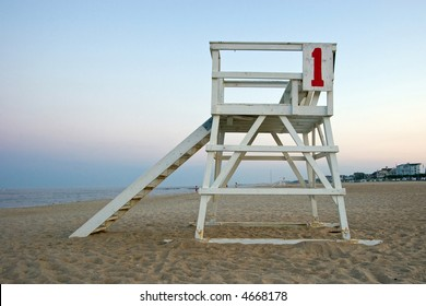 Color DSLR picture of a lifeguard stand on the sand at the New Jersey shore at dusk.  Haze on the calm ocean in background.  Horizontal with copy space for text.