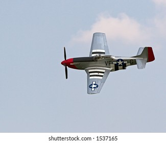 Color DSLR picture of a United States airforce P-51 Mustang WWII fighter plane, flying at an airshow.  Silver propeller airplane is speeding through a blue sky.  Horizontal with copy space for text.