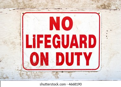 Color DSLR picture of a white sign with red words saying no lifeguard on duty.  Weathered sign is nailed to a wooden wall.  Horizontal orientation with copy space for text.