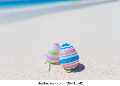 color Easter eggs on the sandy beach by the ocean