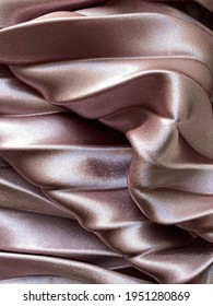 The color of the fabric is dusty pink or powdery. Fabric folds, wavy background
