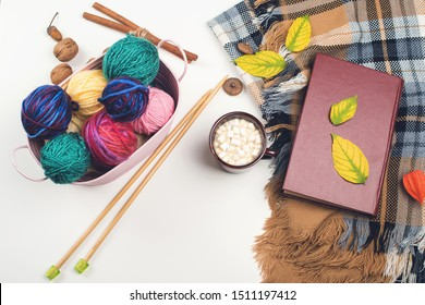 Color fashion yarn in a bascket. Autumn leisure and hobbies. Autumn knitting, knitting needles and wool balls. Autumn composition with hot chocolate, autumn leaves, wool, book.
