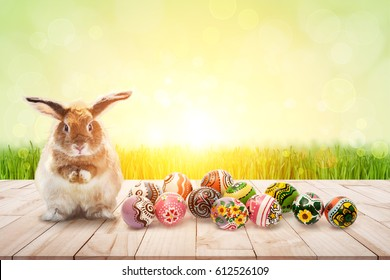 color full easter eggs and Brown Rabbit on wood and green bokeh in flare light for Easter festival Background