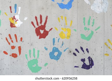 Color hand prints over a concrete wall. red, yellow, green and blue paint. Good as a background image.