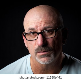 Color head shot of a middle aged man looking into camera with facial hair with a concerned look on his face on a black background
