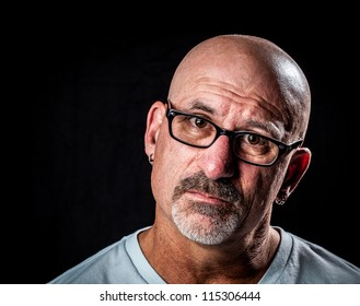 Color head shot of a middle aged man with facial hair and a frustrated look on his face with glasses with on a black background