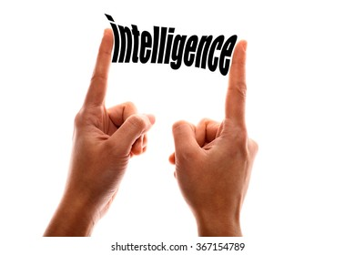 """Color horizontal shot of a hand squeezing the word """"intelligence""""."""