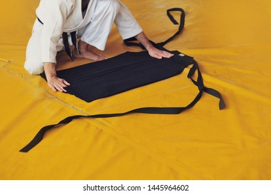 Color image of aikido. The male athlete carefully folds the black hackam. The traditional form of clothing in Aikido.