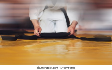 Color image of aikido. The male athlete carefully folds the black hackam. The traditional form of clothing in Aikido. Background blurred image for web pages and printing.