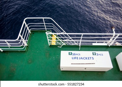 Color image of a box with life jackets on the deck of a boat.