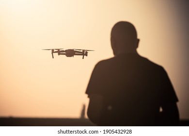 Color image of a man flying a drone at sunrise.