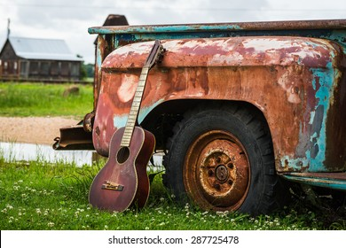 Color image of an old acoustic guitar leaning up against an old rusted truck parked in the grass with an old wood shack in the background in Clarksdale Mississippi