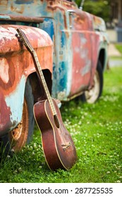 Color image of an old acoustic guitar leaning up against an old rusted out truck parked in green grass in Clarksdale Mississippi.