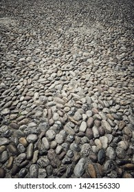 Color image of a pavement made of round stones.