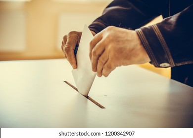 Color image of a person casting a ballot at a polling station, during elections.