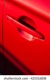 Color image of a red car door handle.