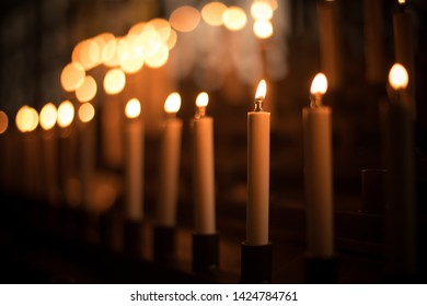 Color image of rows of candles burning in a church.