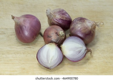 Color image of sliced red onions on brown wooden chop board.Isolated image of red onion or shallot: Asian cuisine ingredient.