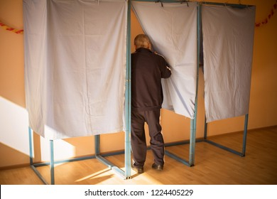 Color image of an unidentifiable person voting in booths at a polling station, during elections.