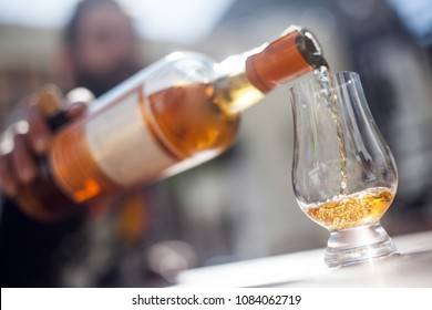Color image of an unrecognizable man pouring whisky from a bottle into a glass.