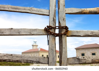 Color image of a wood fence with a lighthouse behind.
