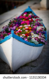 Color image of a wooden boat filled with various flowers.