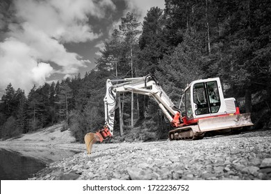 color key of small bucket excavator on gravel shore at lake and forest trees