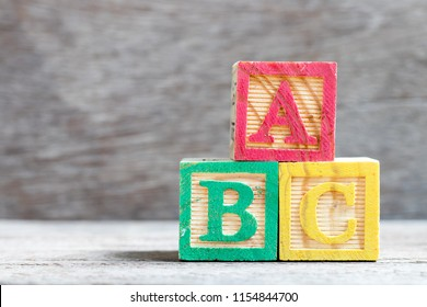 Color letter block in word abc on wood background