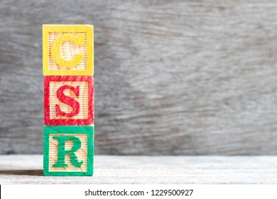 Color letter block in word CSR (Abbreviation of corporate social responsibility) on wood background