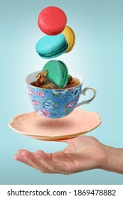 Color macaroons falling in to decorated blue porcelain teacup full of tea levitating over the woman's hand