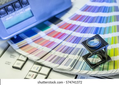 Color management in printing process with magnifying glass, color swatches and densitometer