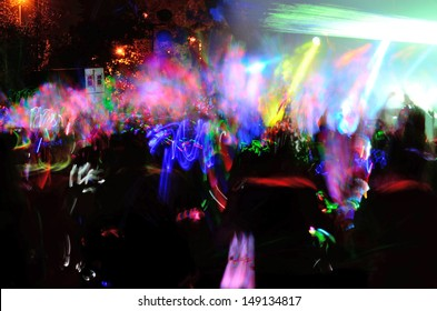 Color neon streaks of light glow sticks at a night celebration and rave