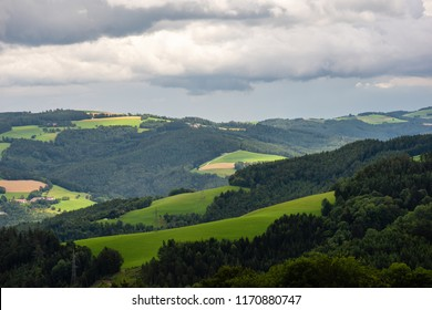 Color outdoor idyllic summer farmland landscape with fields,meadow,trees and forest under a sky with heavy clouds and a view over valleys towards the horizon