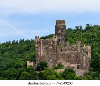 Color outdoor image of the medieval castle / fortress Maus, Sankt Goarshausen, Germany, on a sunny day in summer with blue sky and light clouds surrounded by a green forest