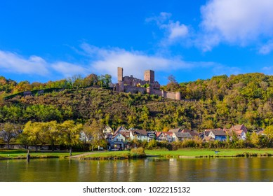 Color outdoor panorama  the ruin of the medieval castle/fortress Henneburg, Wertheim, Germany,sunny bright day in autumn/fall,blue sky,light clouds,autumnal forest,village, river Main
