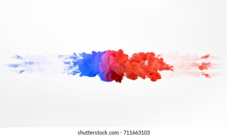 Color paint drops in water. Ink swirling underwater. Cloud of silky ink collision isolated on white background. Colorful abstract smoke explosion. Close up camera view.