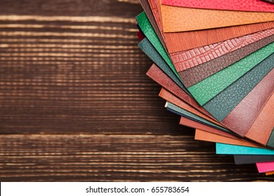 color palette  colored leather on a wooden background. Colorful upholstery fabric samples