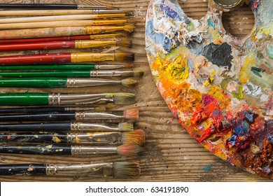 Color palette with different brushes on a wooden floor in a studio.
