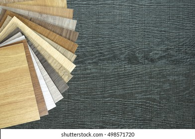Color palette for furniture on table close-up.Samples of laminate and vinyl floor tile on wooden Background.