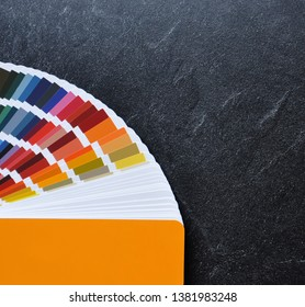 Color palette guide, fan, catalogue on  black background. Ral color fan  with orange cover on stone texture